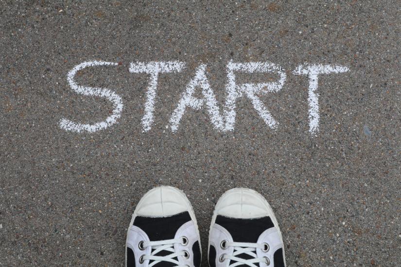Start Schriftzug auf der Straße mit einem paar Schuhen